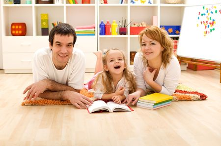 Happy family with a child laying on the floor preparing to read a story in the kids room photo
