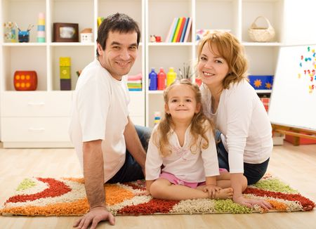 Happy family with a kid sitting on the floor together photo