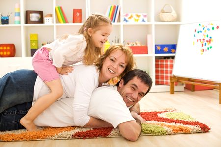 home sweet home: Happy family heap - parents and a child having fun in the kids room