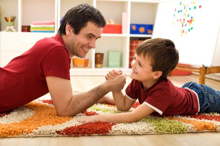 kids' room: Happy boy and his father arm wrestling laying on the floor in the kids room