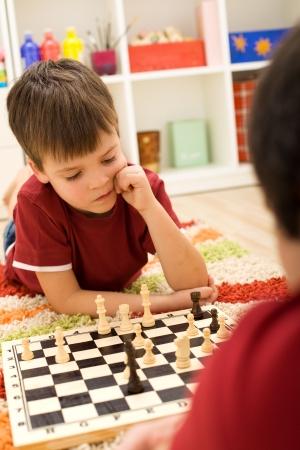 jugando ajedrez: Chico serio jugador de ajedrez pensando en el próximo paso tirado en el suelo