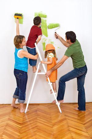 hand schilderen: Opknappen van het huis - de muur schilderij en gelukkige familie  Stockfoto