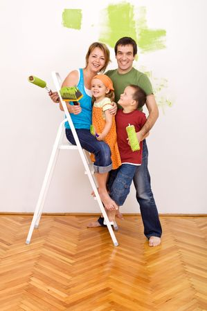 renovation de maison: Famille heureuse avec peinture ustensiles avant leur maison de redecorating Banque d'images