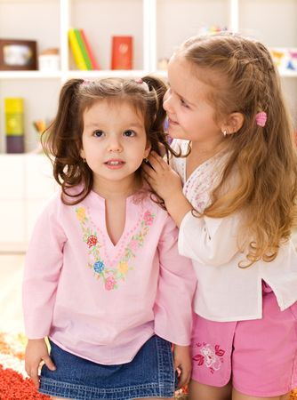 Little happy girls whispering secrets to each other playing in their room photo
