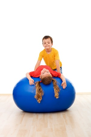 color therapy: Kids doing streching exercises on large rubber ball helping each other - isolated