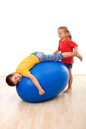 ball stretching: Kids having fun playing with a large rubber exercise ball