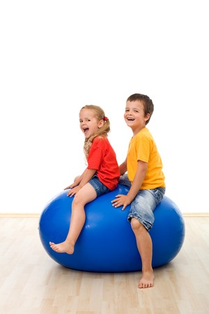 Kids jumping and having fun on a large rubber exercise ball - isolated