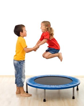 ni�os ayudando: Ni�os que se divierten con un trampol�n en el gimnasio - aislado, movimiento ligero desenfoque