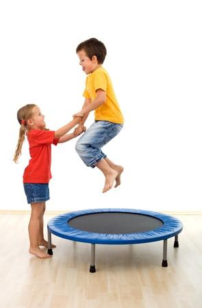 ni�os ayudando: Ni�os que se divierten en un trampol�n en el gimnasio - ayudando mutuamente - aislado