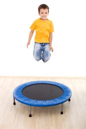 ni�o saltando: Chico saltar alto en trampol�n en el gimnasio - aislado, movimiento ligero desenfoque  Foto de archivo