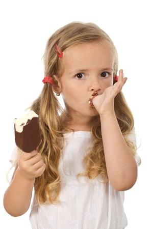 meisje eten: Kleine meid eten van ijs, likken haar vinger - geïsoleerd