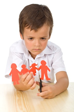 sad child: Divorce concept with sad kid cutting paper people - isolated Stock Photo