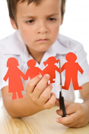 Sad kid cutting his paper people family - divorce concept, closeup
