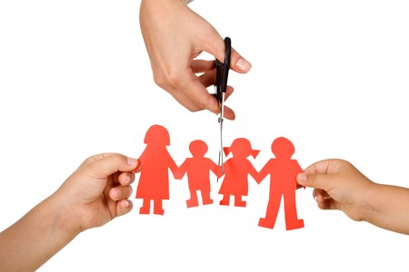 seperation: Divorce effect on kids concept with hands cutting paper people family - isolated