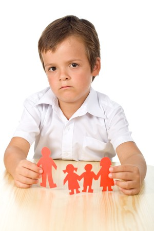 Divorce concept with sad kid holding splitted paper people family photo