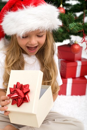 opening gift: Excited little girl opening christmas present in front of the fir tree - closeup