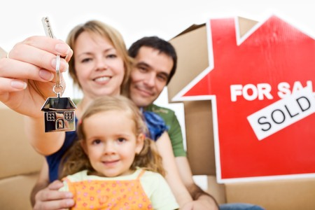 moving in: Happy an proud new homeowners - family moving in their home concept