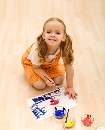 Happy girl painting sitting on the floor - top view photo