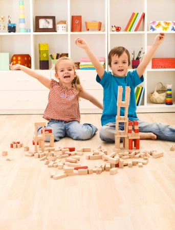 tower block: Kids proudly showing their wooden block buildings, sitting on the floor
