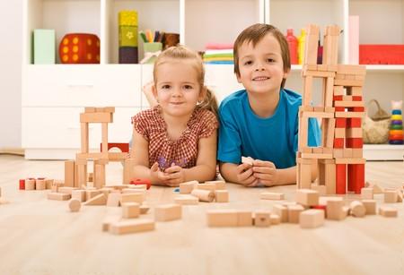 wooden blocks: Happy kids with wooden blocks on the floor in their room