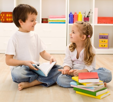 let on: Let me tell you about school - siblings with books talking at home, back to school concept Stock Photo