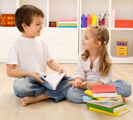let on: Perm�tanme decirles acerca de escuela - hermanos con libros hablando en casa, volver al concepto de escuela  Foto de archivo
