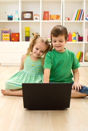 computer game: Kids with laptop, sitting on the floor playing Stock Photo