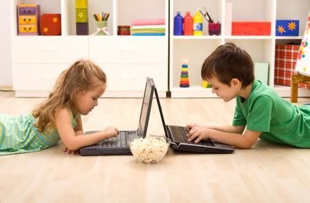 Dzieci z komputerów przenośnych i bowl popcorn odtwarzanie na podłodze