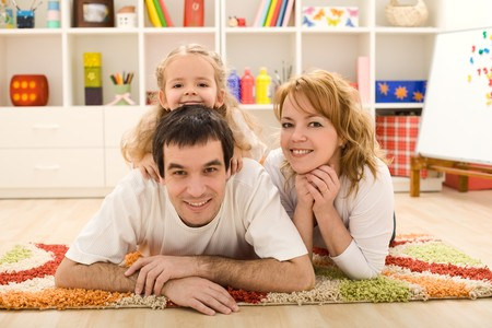 holiday home: Happy family laying on the floor in the kids room - focus on the little girl