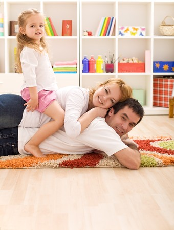 Happy couple with a child in the kids room having fun Stock Photo