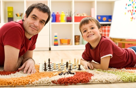 Happy boy proud of his achievements taking chess lessons from the father photo