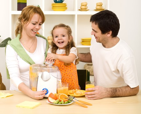 extractor: Happy family with a kid making fresh fruit juice from oranges - healthy diet concept