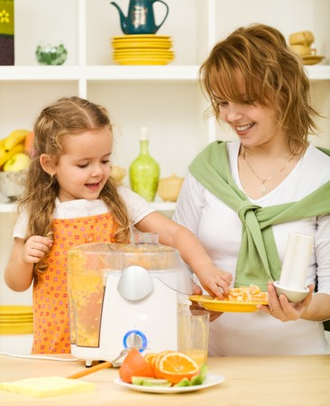Little girl and woman making fresh orange juice - healthy life concept
