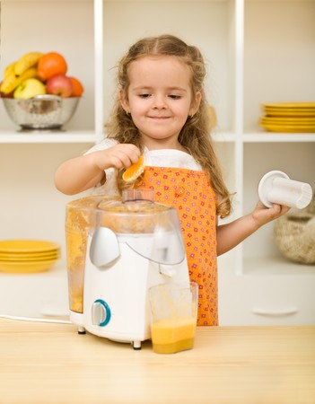Little girl making fresh orange juice in the kitchen photo