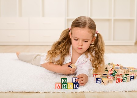 Little girl playing with wooden alphabetic blocks on the floor photo
