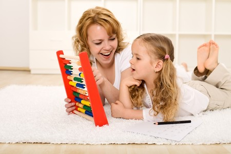 subtract: Little girl doing math exercises with her mother at home