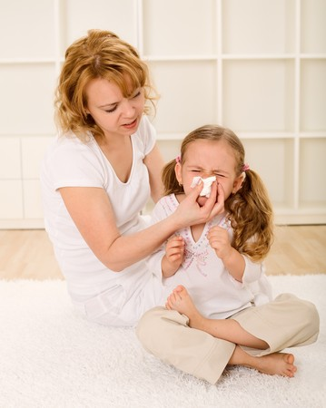 Little girl blowing nose with her mother helping photo