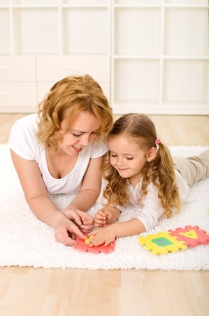 Woman and little girl playing on the floor with alphabet puzzle pieces photo
