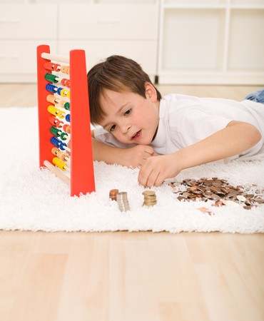 counting: Little boy counting his savings laying on the floor with a pile of coins and an abacus
