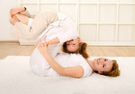 female wrestling: Woman and little girl having fun on the floor with exercises and wrestling