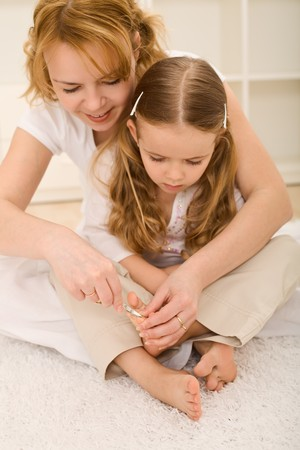 Personal grooming - woman and little girl cutting toe nails Stock Photo - 7857323