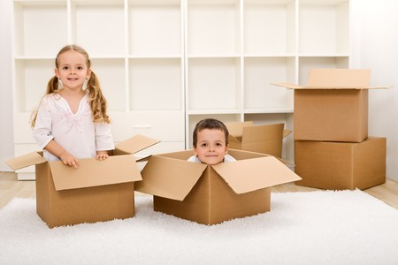 moving home: Kids in their new home having fun with cardboard boxes