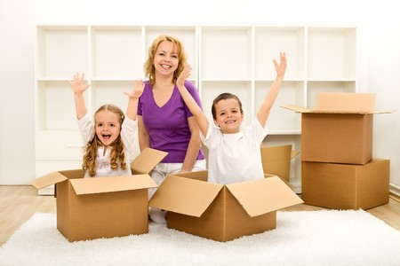 people moving: Happy family moving into a new home - with cardboard boxes in an empty room Stock Photo