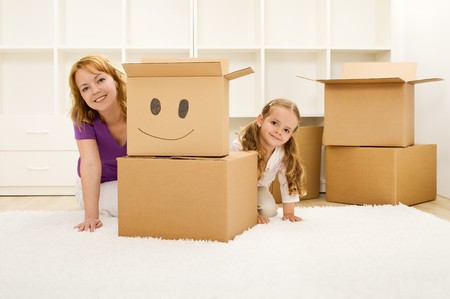 Happy woman and little girl unpacking and having fun in a new home photo