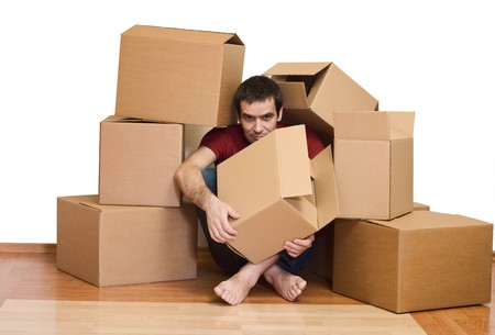 overrun: Man overrun by the issues of moving - covered with cardboard boxes Stock Photo
