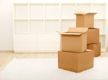 unpacking: Cardboard boxes in front of empty shelves in a room - moving concept