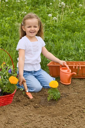 Little smiling girl gardening - planting flowers outdoors photo