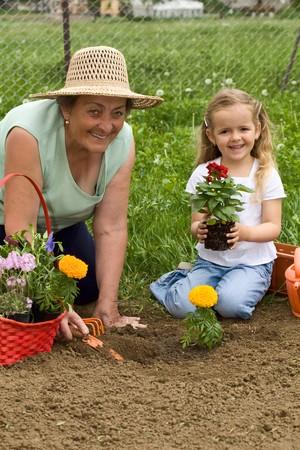 Grandmother teaching little girl gardening - planting a flower together