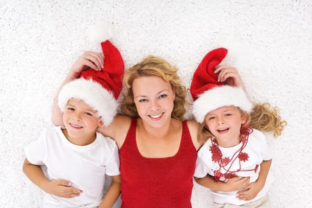adult christmas: Woman and kids laying on the floor at christmas time wearing santa hats