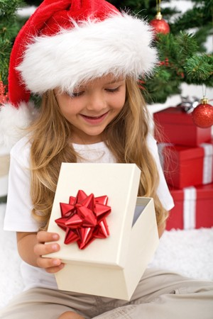 receive: Little girl opening present in front of christmas tree - closeup Stock Photo